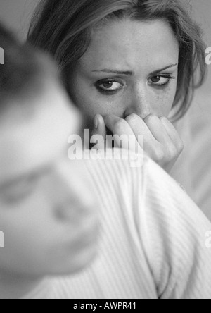 Tearful woman with hand against mouth, looking at man, close-up, b&w - Stock Photo