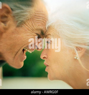 Senior couple arguing, foreheads touching, close-up - Stock Photo