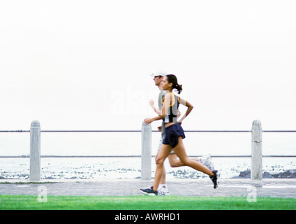 Couple jogging, sea in background, side view. - Stock Photo