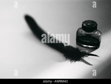 Quill pen and bottle of ink, b&w. - Stock Photo