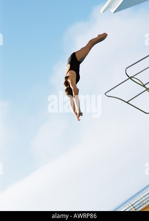 Woman in mid-dive, low angle view, full length, blue sky in background - Stockfoto