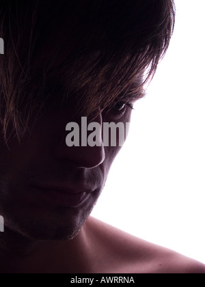 Close-up of the face of a serious young man in backlight - Stockfoto
