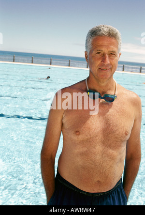 Mature man in front of swimming pool, portrait - Stock Photo