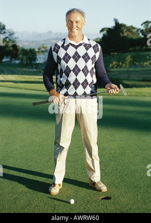 Mature man holding golf club next to hole, portrait - Stock Photo