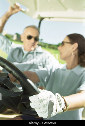 Mature man and woman in golf cart, close-up, focus on hand and steering wheel in foreground - Stock Photo