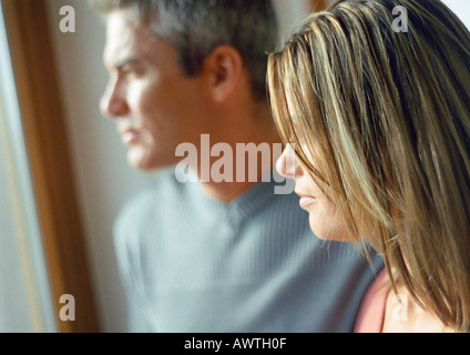 Man and woman, side view, head and shoulders, natural light on faces, close-up - Stock Photo
