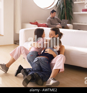 Woman being hugged by two children, man working on laptop in background - Stock Photo