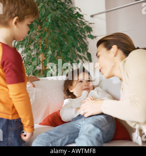 Woman holding daughter on couch, son standing nearby - Stock Photo