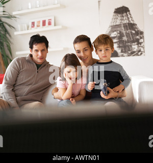 Family sitting on the couch, rear view of tv in foreground, blurred - Stock Photo