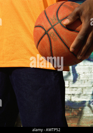 Man holding basketball, close-up - Stock Photo