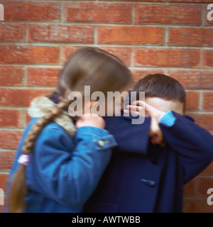 Girl trying to kiss boy, boy covering face with arms, blurred - Stockfoto