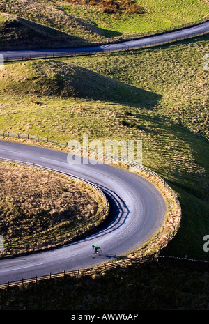 A cyclist on a s bend on Mam Tor near Edale in the Peak District National Park Derbyshire England United Kingdom - Stock Photo