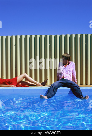 Man and woman relaxing by swimming pool, man dipping feet in water - Stock Photo