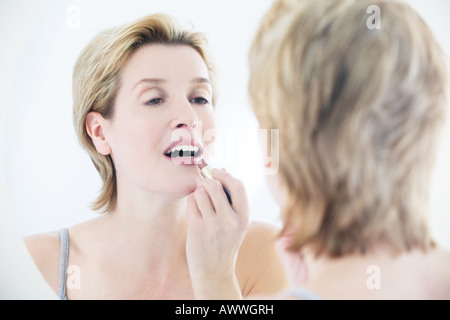 A woman applying lipstick in the mirror - Stockfoto