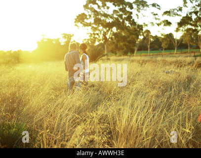 Couple standing in field of tall grass, rear view - Stock Photo