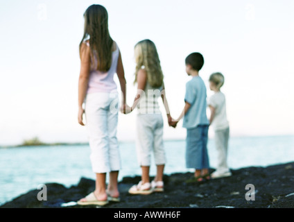 Children standing, holding hands, looking out to sea - Stock Photo