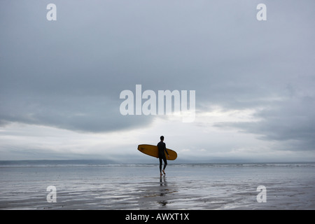 Surfer carrying surfboard on beach, back view - Stock Photo