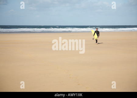 Surfer carrying surfboard walking on beach, back view - Stock Photo