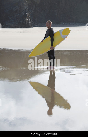 Man carrying surfboard on beach, side view - Stock Photo