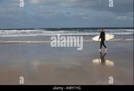 Man carrying surfboard walking on beach - Stock Photo