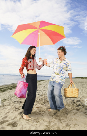 Couple preparing to picnic at the beach - Stock Photo