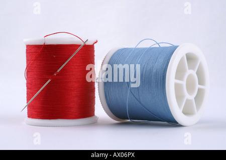 Cotton crafts cotton reels in red an blue with needle / Nähgarn Garn Stopfgarn in blau und rot mit Nadel - Stock Photo