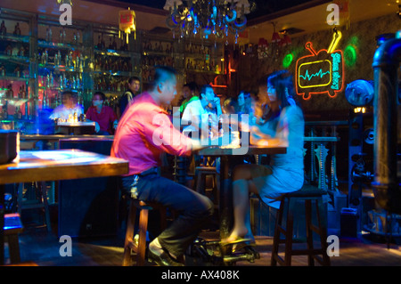 China, Hainan Province, Hainan Island, Sanya City. Chinese couple drinking in a nightclub. - Stockfoto