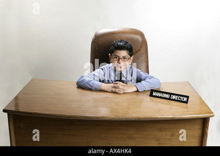 Portrait of a boy sitting in an office and pretending like a businessman - Stock Photo