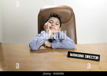 Portrait of a boy pretending like a businessman and looking sad - Stock Photo