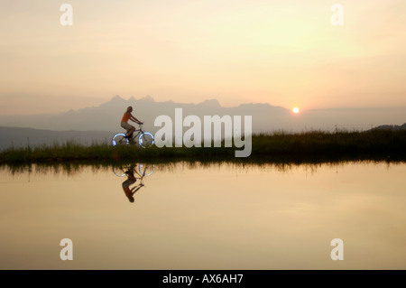 Austria, Alps, Woman riding bicycle by lake, side view - Stock Photo