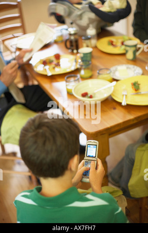 High angle view of a boy sitting at a dining table and using a mobile phone - Stock Photo
