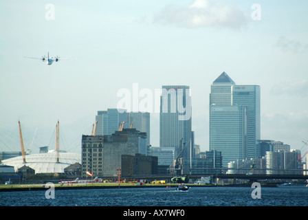 East London passenger plane taking off from City Airport above redundant Royal Albert Dock waters Dome & Canary - Stock Photo