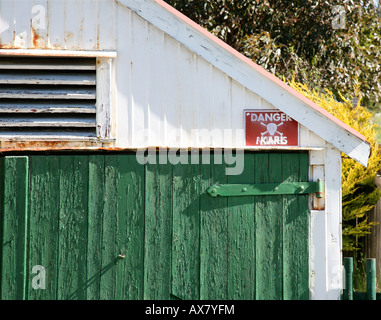 garage/shed with green door and sign on wall - Stock Photo