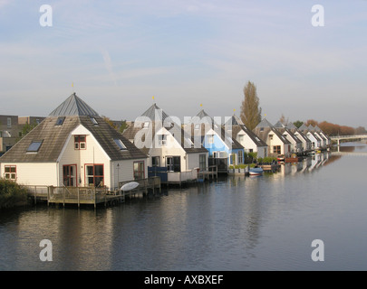 Row of identical Residential houses in modern architecture by the waterside Almere Buiten Netherlands - Stock Photo