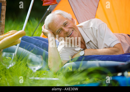 Senior man relaxing in tent, portrait - Stock Photo