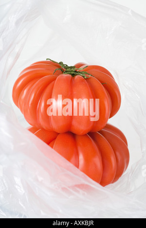 Heirloom tomatoes in plastic bag, close-up - Stock Photo