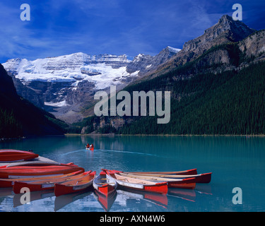 Red canoes on Lake Louise with Mount Victoria and Victoria Glacier reflections in Banff National Park, Canada - Stockfoto