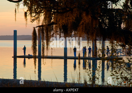 group of tourists and lone fisherman standing on boardwalk during sunset near hilton head south carolina united - Stockfoto