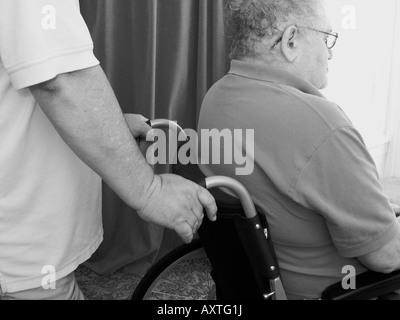 male carer son pushing elderly man in wheelchair - Stockfoto