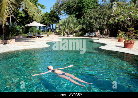 A woman sunbathing in a pool at a hotel resort dead sea israel stock photo royalty free image for Hotels in jerusalem with swimming pool
