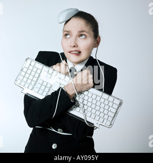 studio shot portrait of a beautiful young woman in a costume suit attached to a computer keyboard and been attack - Stock Photo