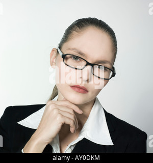 studio shot portrait of a beautiful young and strict woman in a costume suit - Stockfoto