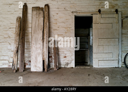 Planks of wood against a bricked wall in a garage - Stock Photo