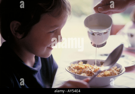 Young boy having breakfast of cornflakes and fresh milk - Stock Photo