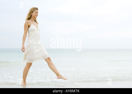 Young woman in sundress taking large step as she walks in shallow water on beach, full length - Stock Photo