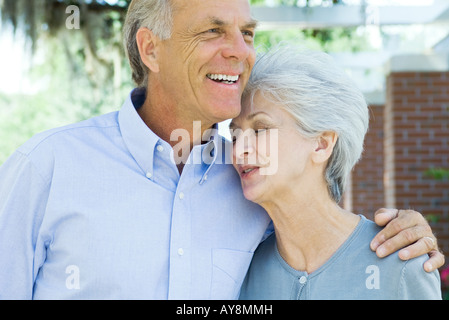 Mature couple embracing, woman's eyes closed, both smiling - Stock Photo
