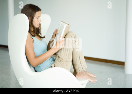 Teenage girl sitting in chair, reading book, side view - Stock Photo