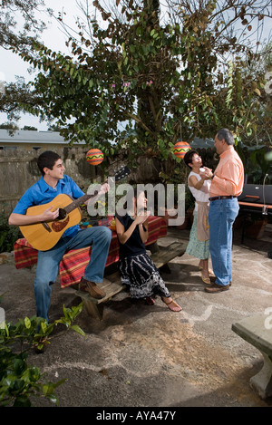 Mexican mother playing with her children in front of the for American house music