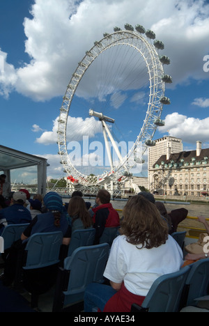 London River Thames passengers on tour boat with Shell centre and British Airways Millennium eye Ferris wheel beyond - Stock Photo
