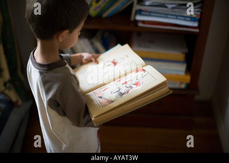 Boy aged six years reads book of Fairy Tales and Nursery Rhymes - Stock Photo